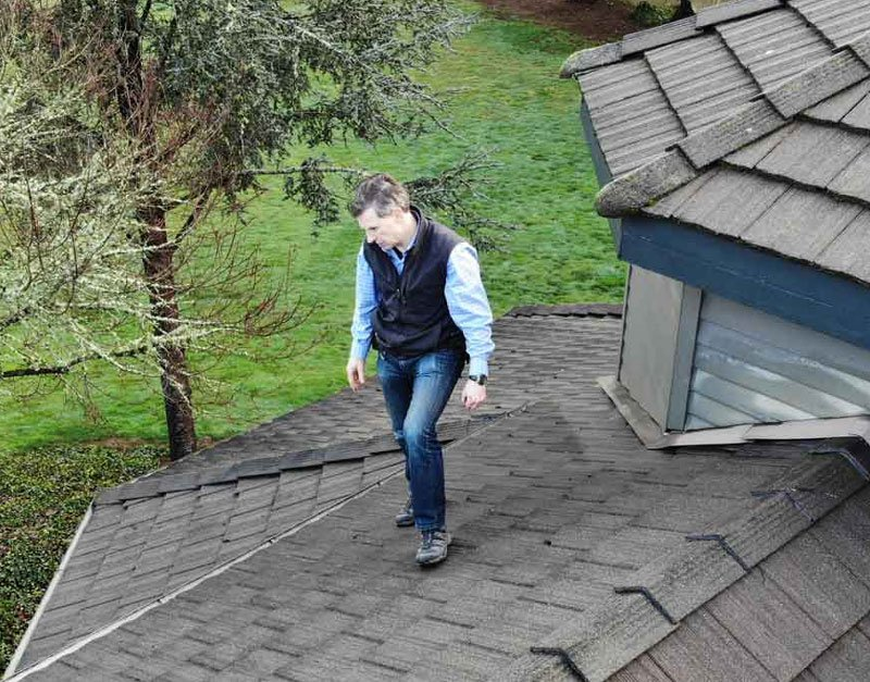 Craig Poindexter, home inspector, inspecting a roof.