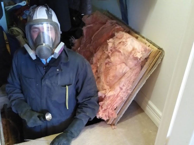 A home inspector emerging from a crawl space wearing a ventilation mask
